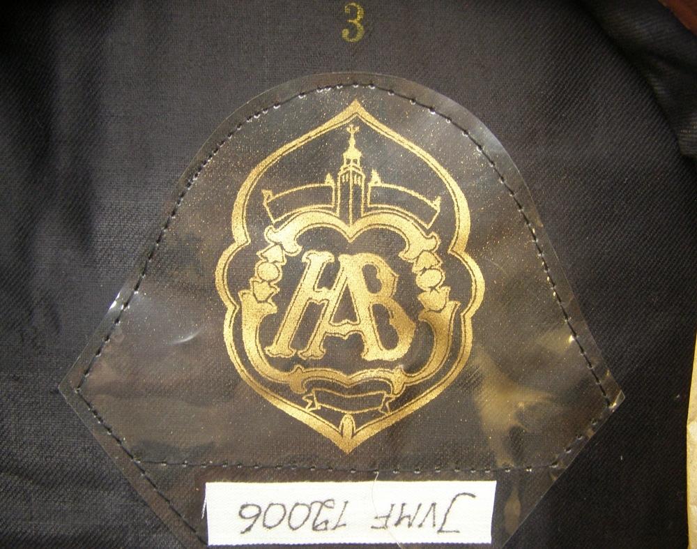 Skärmmössa av kläde med broderat mössmärke. Högrött jaquardvävt 35 mm silkesband.  Storlek 3.