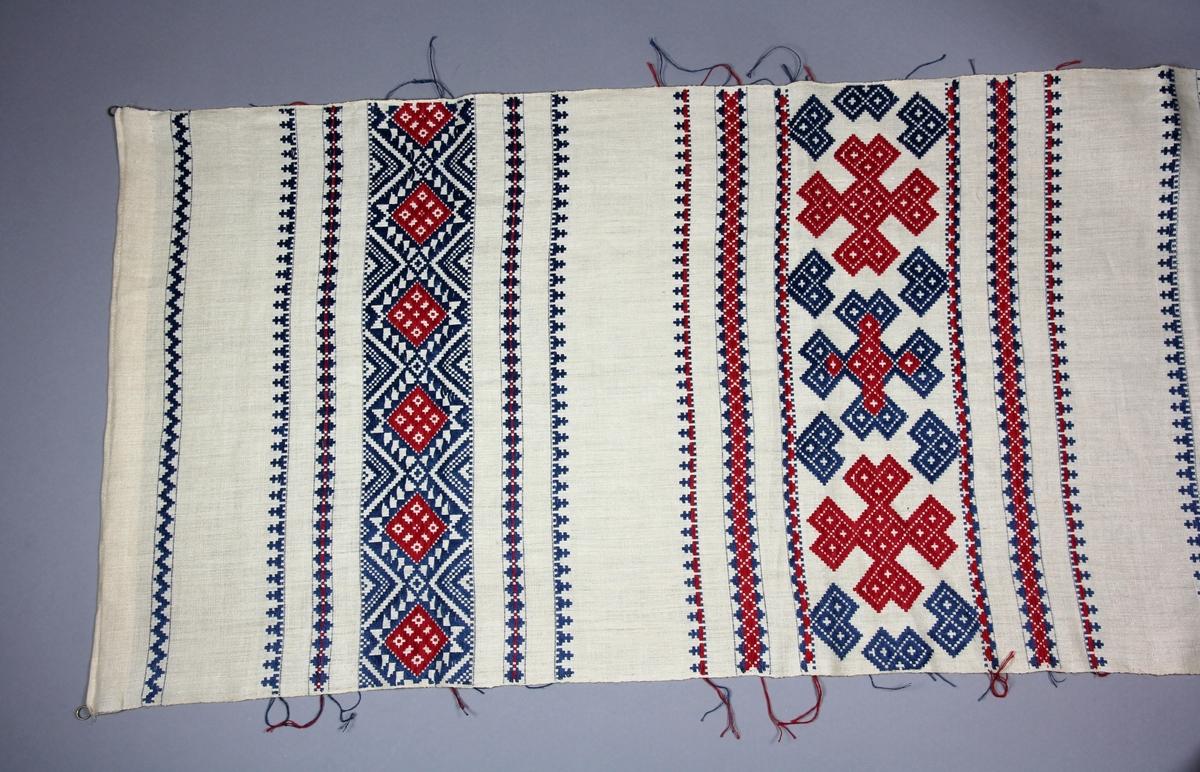 Hängkläde, handvävt, med linvarp och inslag i lin och bomull. Botten i tuskaft, plockade bårder i upphämta i rött och blått. Bårderna med rutmönster och stjärnor. Kopia av NM.0017603 från Blekinge.