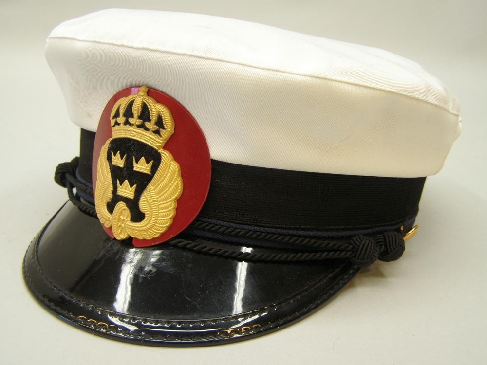 Skärmmössa storlek 57 med vitt sommarkapell. Röd plåtbricka av lättmetall, bakom mössmärke för uniformspliktig personal.