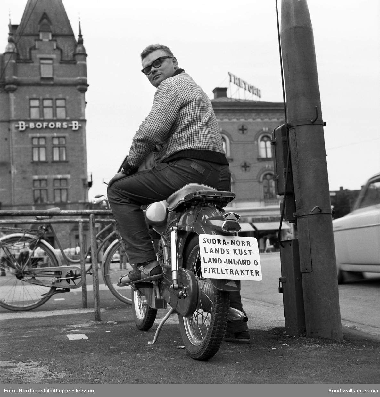 """Lennart Berg på torget med sin moped med skylten: """"Södra Norrlands kustland inland o fjälltrakter"""""""