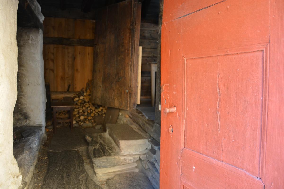 """Bygning med to rom: eldhus / """"utdør"""" i reisverk og sjølve stoverommet i laft. Grue i eldhusdelen.  Liggande panel utvending, med unntak av eit stykke på eine langveggen som har ståande panel.  Raudmåla. Torvtak."""