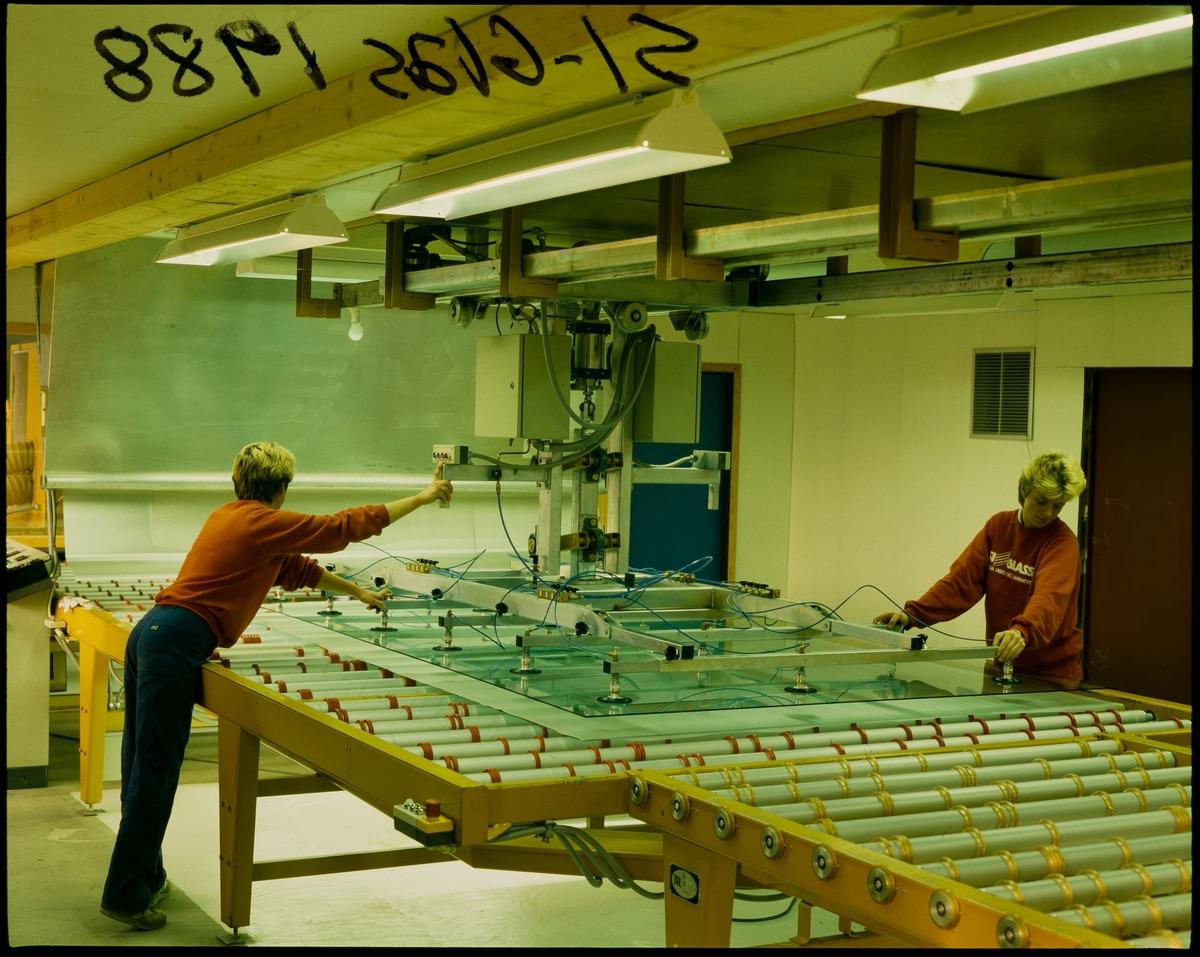 To kvinner produkserer sikkerhetsglass på en fabrikk i Sauda.