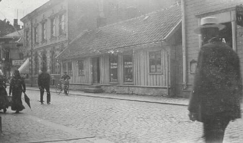 """Bild 1: Foto efter 1912-07-04, då Albert Skantze fick föreläggande att anordna takrännor och stuprör.  Skyltfönster tillkom 1909 o 1910.  På skylten står N.Åkesson Skrädderiaffär.  På baksidan av org.bild 2 står det """"Fröken Maria Johansson Storgatan 60 (=37) Falkenberg"""" """"Till minne af Skusgthus"""" """"fåt af Sofia År 1912"""""""