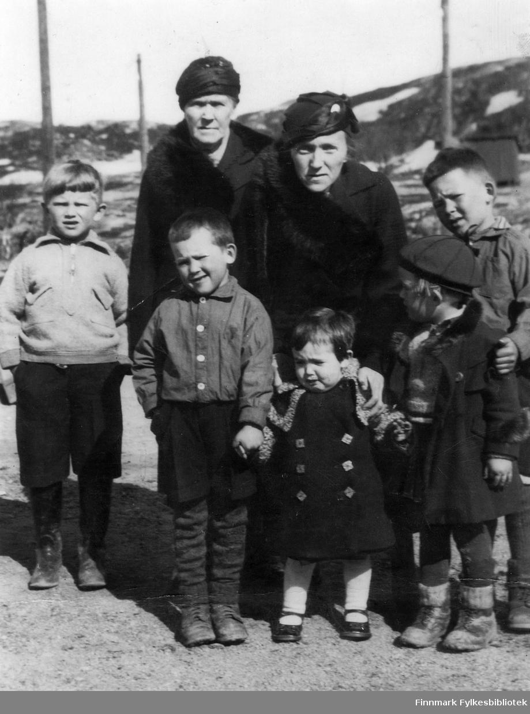 Martin Seljemo til venstre, er avbildet sammen med Hårek Isaksen, Liv Isaksen, Totto Isaksen, og Einar Isaksen. Bak står Mina Strøm, og Marja Strøm. Bildet er tatt på en vei i Bjørnevatn.