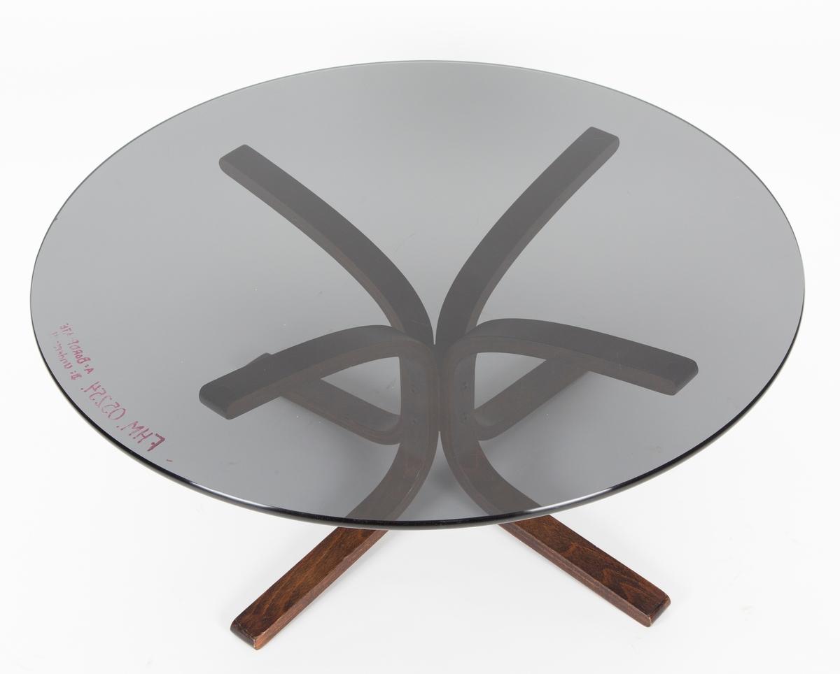 Rund sotfarget glassplate hviler på ben av laminert tre, fire ben.