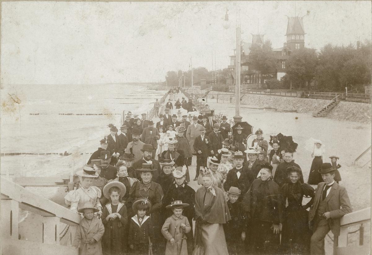 Fotografi av en eller annen tilstelning på strandpromenaden i Kranz, nå Zelenogradsk. I forreste rekke står Valentine og Ignazy Rostin som nr. 2 og 3 fra venstre. Øvrige personer er ukjente. Bak sees Kranz damebad med det karakteristiske høye tårnet. Familien Rostin ferierte ofte i Kranz, og Victoria ble født der, antagelig 1897.   Bildet er tatt 12.sept 1897.