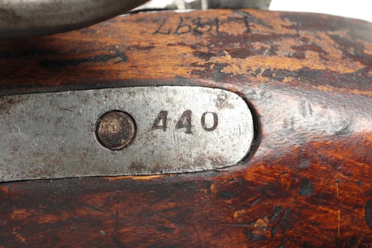 """Slaglåspistol med pipa av stå. Stock och kolv av trä. Kolvkappa, varbygel och pipband av mässing. Låset är utrustat med varhake. Sidoblecket och bälteshaken är tillverkat i samma stycke. Låsblecket är stämplat med """"H 1848"""". I kolven sitter flottans kassationsstämpel inbränt i form av kors med ring. På pipan finns ett mässingskorn, och undertill en laddstock i stål. Stocken försedd med en pistolsnoddsring. Pipan är slätborrad med en innerdiameter på 16 mm.  Inskrivet i huvudkatalog omkring 1880"""