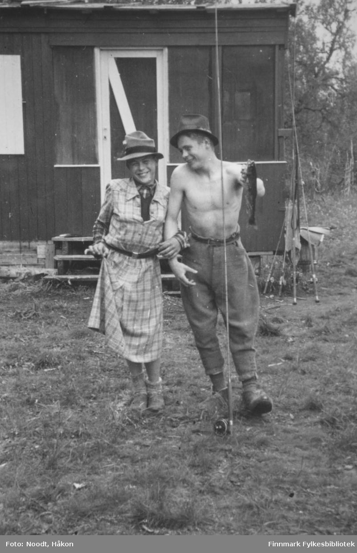 Erik og Ivar Noodt har det moro med dameklær og fiskestang. Ivar holder en fisk, kanskje ørret, i hånda. Bildet er tatt utenfor Leif Noodts hytte i Stabbursdalen i Porsanger, 1954.