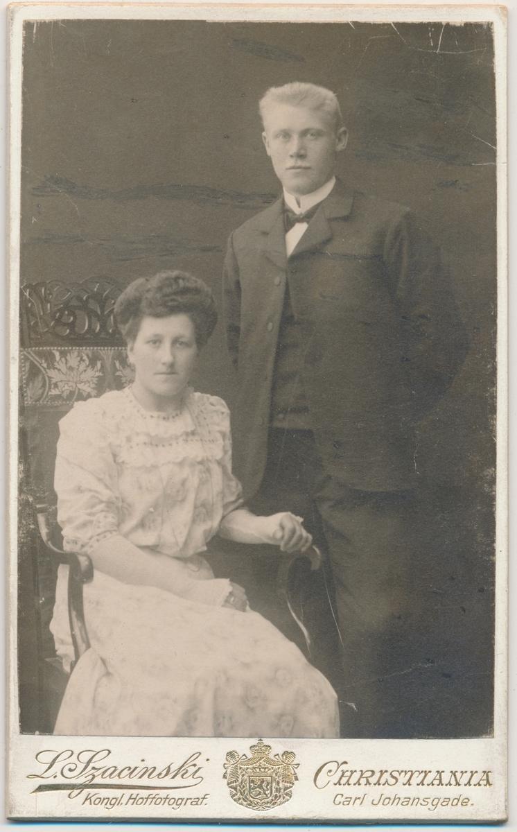 Ungt par, han stående og hun sittende - brudebilde?, ukjente