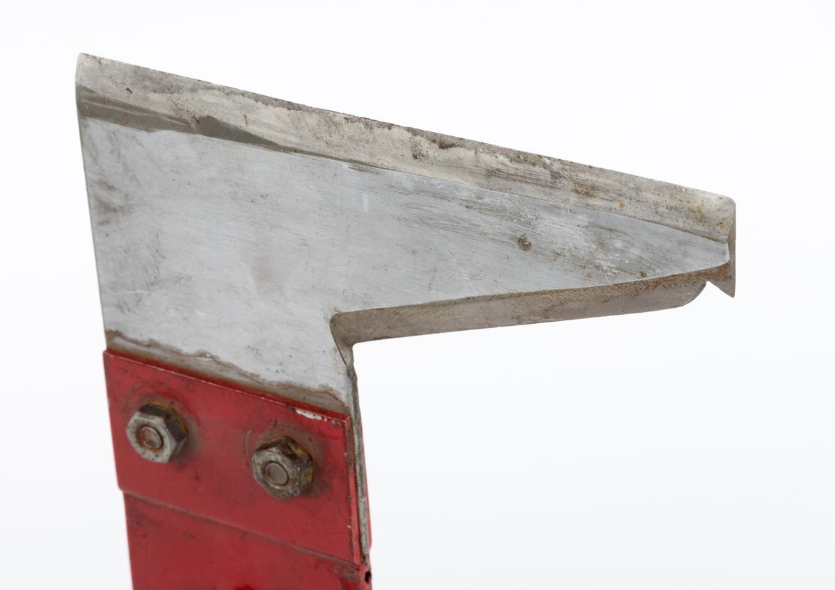 Eggredskap, antakelig en kniv som skulle monteres på et langt skaft og brukes til å kappe kvistene av ungfuru med sikte på å skape et tre der rotstokken etter avvirkning kunne selges som kvistfri. Slikt tømmer kunne for eksempel brukes i finérproduksjon, og rettvokste, kvistfrie stokker har gjerne ligget høyt i pris.   Sett fra sidene har denne gjenstanden L-form. Den er sammensatt av to elementer: Et vinklet blad og en skaftholk. Bladet er lagd av ei drøyt 2 millimeter tjukk stålplate. Det er festet ved hjelp av to skruer i ei slisse i de fremre enden av et fal-beslag, som egentlig består av to formpressete plater. Disse er lagt mot hverandre og punktsveiset, slik at den har fått en gradvis smaknende fal fra den øvre endeflata og cirka 12 centimeter nedover. Øverst i denne falen er det et gjennombrutt hull, antakelig for en skrue eller en spiker, som skulle sikre at kvistekniven satt godt på skaftets endetapp, uansett i hvilken retning man skar kvisten. Den fremre egglina på bladet er drøyt 14,1 centimeter lang, og den er sakseslipt. Denne eggen kappet kvisten fra undersida når man støtte skaftet (som denne kniven antakelig ikke har fått) oppover langs trestammen. Den noe kortere eggen motsatt side (ca. 9 centimeter), på den utstikkende delen av bladet, skråner noe i forhold til den førstnevnte egglinja, men er likevel i hovedsak rettlinjet. Unntaket er et lite hakk i den ytre enden. Denne eggen ble antakelig brukt når kvisten ble skåret med «nedovernappende» rykk.  Kniven og skruene den er festet med er stålblanke. Beslaget med skaftfalen er lakkert med signalrød farge. Gjenstanden har ikke noe produsentstremplel. Det finnes limrester etter en merkelapp på falens ytterside, men vi vet ikke hva det kan ha stått på en slik kllpp  Da denne gjenstanden var utstilt i skolemuseet på Sønsterud skogskole, var den plassert i gruppe med barkespadene. Kniven kunne naturligvis brukes i slikt arbeid også, men registrator tror at den, som antydet, primært er beregnet på fjernin