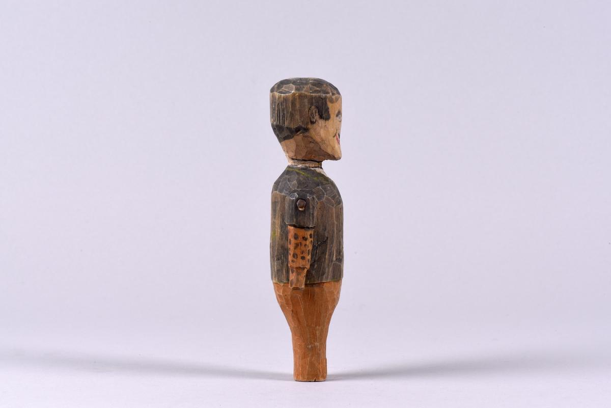 Mansdocka skuren i trä. Utskuren i ett stycke förutom armarna. Bemålad med svart kort hår och mustasch, samt klädsel i form av en svart kavaj, bruna byxor och gul- och svartrandig slips. Ena kavajärmen är uppkavlad.