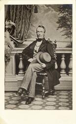 Porträttfoto av en man i mörk redingot med ljus väst och lju