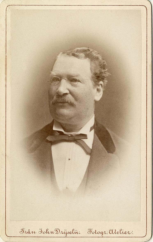 Porträttfoto av en man med glasögon, klädd i kavjkostym med sammetskrage, väst, stärkkrage och fluga.  Bröstbild, halvprofil. Ateljéfoto.