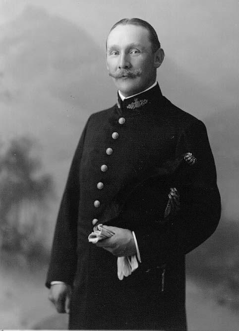 Porträtt av landsfiskal B Carlsson. Han bär uniform, håller mössan under armen och ett par ljus handskar i handen.