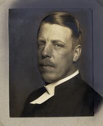 Foto av en man i prästrock och prästkrage.  Bröstbild, halvp