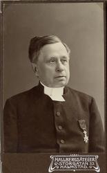 Foto av en medelålders man i prästrock och prästkrage. På br