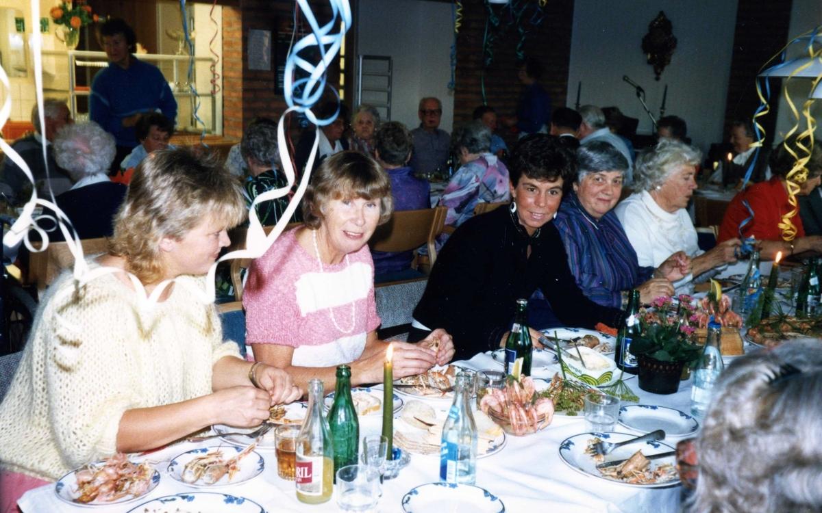 Kräftskiva i Brattåsgårdens matsal (Streteredsvägen 5) där girlanger hänger i taket, 1990-tal. Andra person från vänster: vårdbiträde Greta Nilsson och vårdbiträde Lillvi Häggsten.