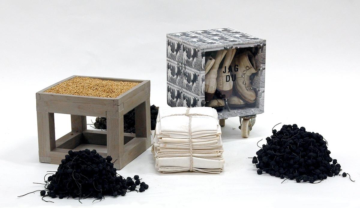 """Objekt """"I mammaminne mammaminne I"""" av Lena Wennberg. Består av stapel i fyra delar. Underst: gråmålat träpodium täckt av sädeskorn. Ovanpå detta en trälåda på snurrhjul. Två sidor samt topp och botten täckta av bilder (foton) av en ko. Två sidor täckta av plexiglas som visar innehållet: ett antal vita skor och skridskor. På lådan en packe vikta, vita handdukar och som krön en packe nedhängande, gjutna, mörka kulor uppträdda på trådar. Text på lådans fyra sidor: """"JAG DU""""  """"HAN HON""""  """"DEN DET"""" och """"VI NI""""."""