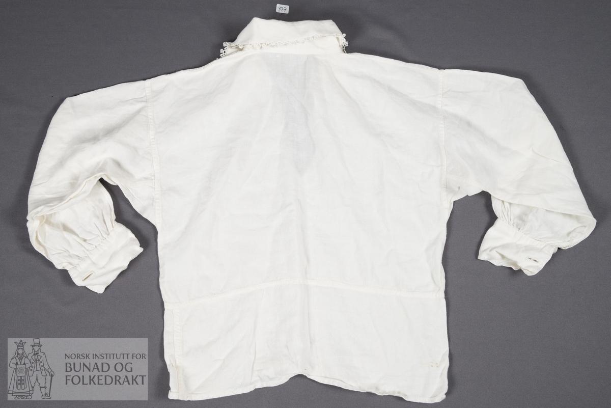 Barneskjorte av hvit lin. Krage kantet med nupereller. Glatt isydde ermer, kile under ermet. Ermene er rynket til mansjettene. Splitt nederst på ermene, mansjettene har to knapphull hver, ett på hver side av splitten. Halssplitt midt foran. Maskinsøm, med noen håndsydde detaljer.