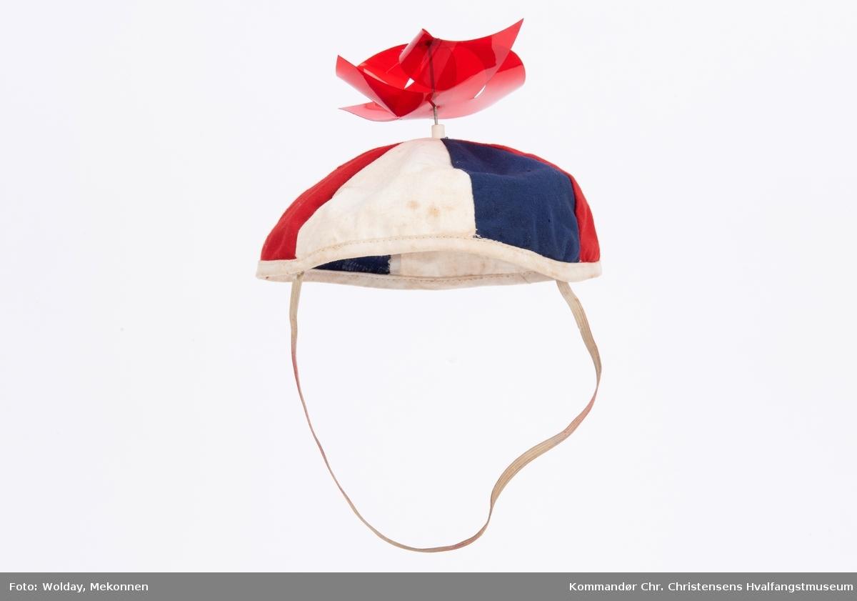 """luen er sydd sammen av 6 trekantede bomullsbiter (rødt, hvitt og blått) påsatt strikk (til feste under haken). En """"propell"""" i plast på toppen."""