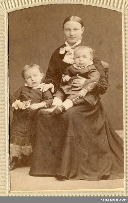 Porträtt av Anna Charlotta Petersson, klädd i mörk klänning, med två av sina barn.
