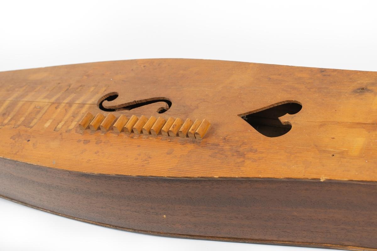 Utbuktende kropp med konvekse sidestykker. Skruekasse med rett brett i forlenging av kroppen. Seks stemmeskruer (gitar/mandolin-skruer) av metall. Tverrbjelke under lokket, synlig gjennom lydhull. Enkelt f-lydhull og et hjerteformet lydhull. 15 tverrband (mangler). 13 noter ved siden av f-lydhull. D-dur. Notesadel oppe og nede (mangler). Strenger (mangler): 1 melodi, 5 bodun. Vurdert strengefeste, ni hakk på notesadel nær stemmeskruene, fem på nedre ende. Fire metallfester på nedre endevegg. Ben oppe og nede (mangler).  Lite eller ingen bruksmerker/slitasje etter spill.