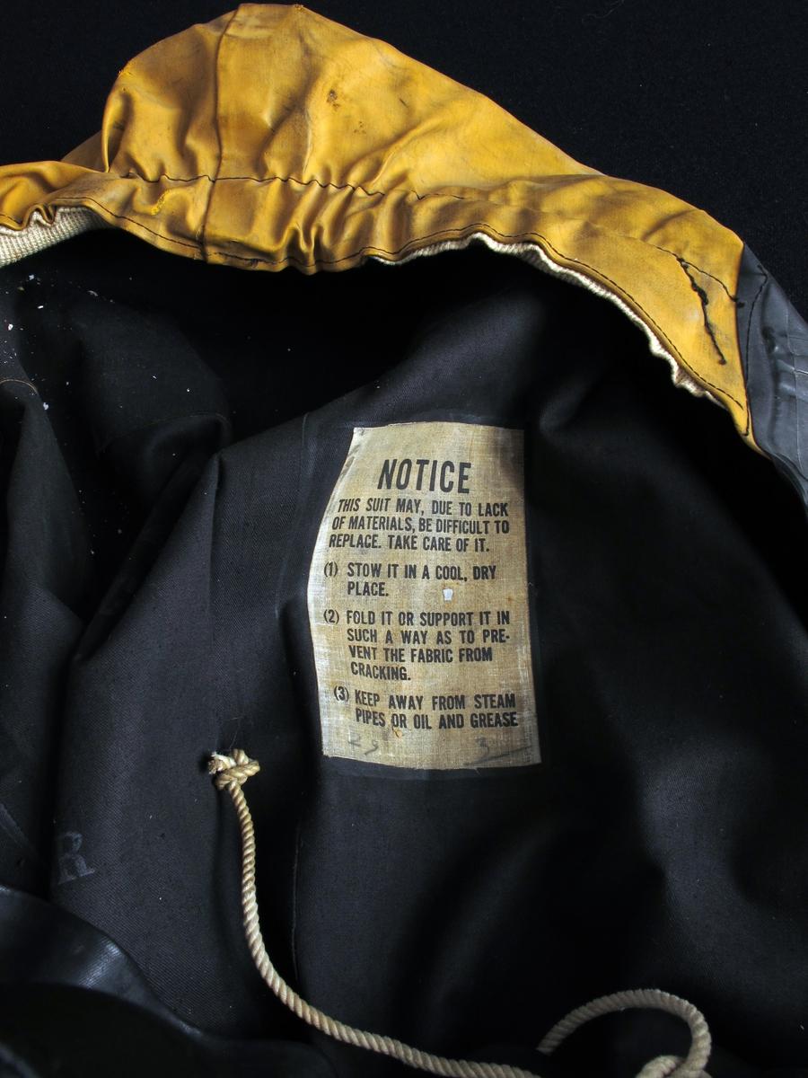 Gummidress, brukt av alliert marine og handelsflåte under krigen 1940 - 45.  Sort dress med gul hette. Stor gummiddress med påsatte støvler, som har blyinnlegg for å holde drakten flytende loddrett. Lange ermer, vid halsåpning med snoretrekk og gul hette med innvendig hvit elastikk. Innv. bruksanvisning.  Stempel under sålen.
