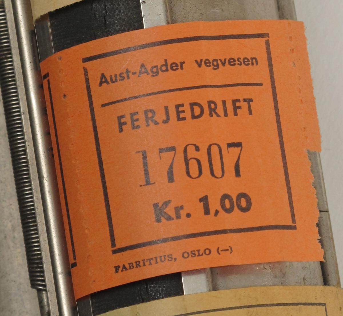 Billettholder, fra ferge.  Forkrommet metall, fabrikkstempel: Fabritius. Sylinder, med 6 ruller billetter,  gradert fra kr. 0,10 til kr. 1,50.