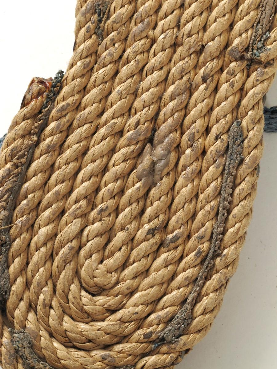 Sandaler,  fra krigen 1940-1945. Såle av papirtau, innlegg av papirstrie, helkappe   og forstykke av papirstrie i naturfarget med blå   bånd. Celluloselim og trådstift. Størrelse 26. L. såle 20. Med spenne.