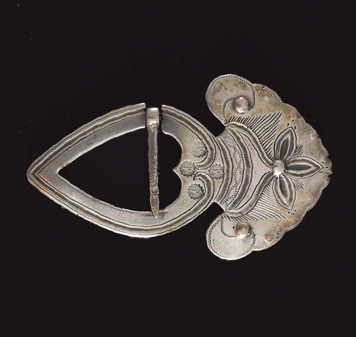 """Hjartesprette i sølv, drevet og gravert. Stemplet 4 ganger på forsiden, plassert som et ornament omkring toppen av hjertet: Hjerteformet flat spenne med hulkil langs kanten, ender i to buer mot hverandre  øverst i hjertet ved stemplene. Stort vifteformet overstykke med tunget kant,  trebladet """"blomst"""" pm. med opphøyd midtknapp,  en tilsvarende på hver side og små langs kanten strekdekor. Nederst på viften en innprikket bord av to motgående bølger. Tilstand: god."""
