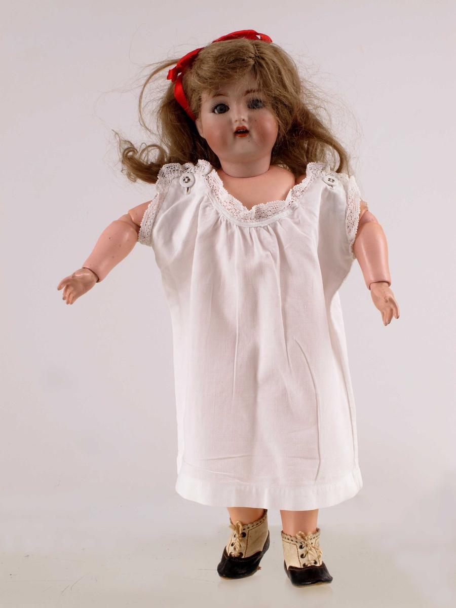 Dukke med brunt hår, øyne som lukkes når den ligger, leddete armer og bein, med fjærer. Påmalt lepper, øyenvipper og øyenbryn. Rødt hårbånd.