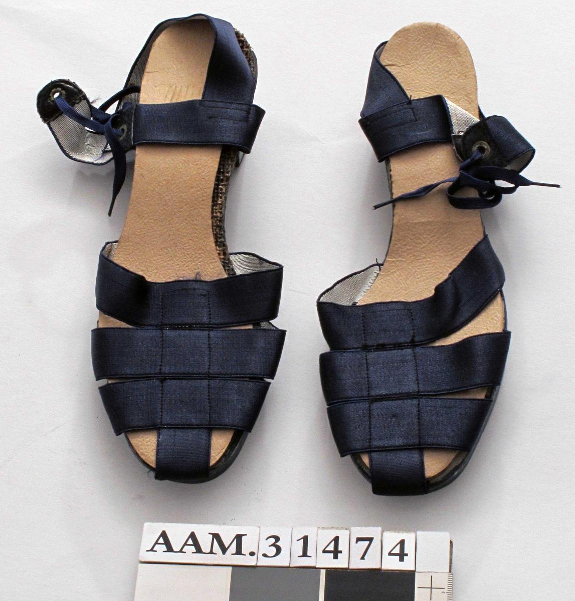 """Et par blå damesko med lave kilehæler.    Skoene har tresåler.  Sålene har innskårne sprekker i sålen for økt fleksibilitet. Innersåle av papor og grov tekstil limt lagvis.  Blåmalt såle og hæl.  """"Overlær"""" er av sammensydde remmer i nylon: tre på tvers og en på langs over tærne, en rem med knytting over vristen og en rem bak hælen.  Størrelse 35"""