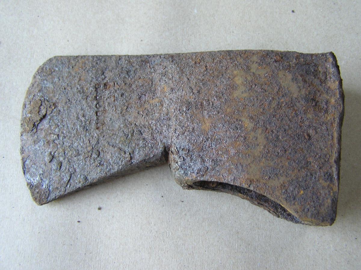 Øks uten skaft. Kun stålsatt i Bodinsmia; jfr. plasseringen av stempelet. Dersom øksa hadde vært laget i Bodinsmia hadde stempelet vært plassert oppe ved nakken.Tildels mye rust.