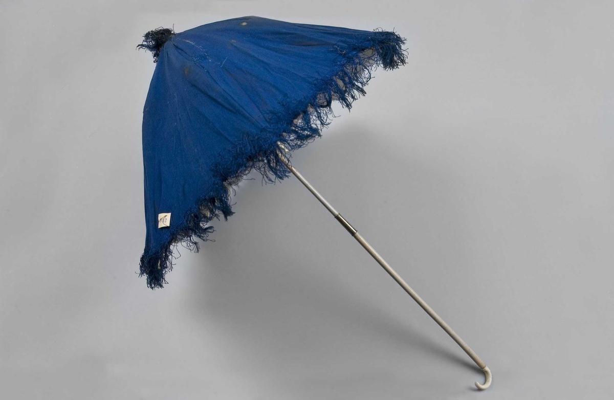 Liten blå parasoll med frynser langs kanten og på toppen. Foret med hvit silke. Spiler med pynteknotter. Stangen er todelt og låses med et messingbeslag, dekorert håndtak.