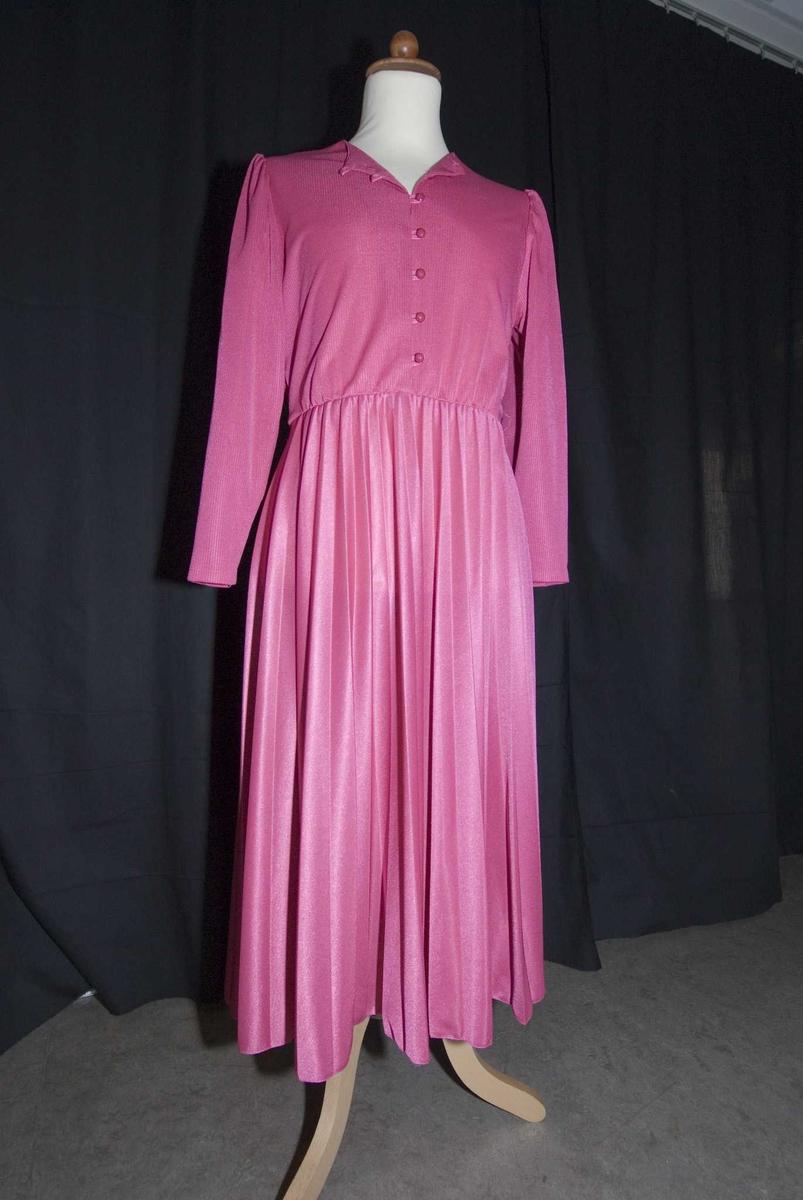 Rosa kjole med lange ermer og foldet skjørt. Uten krave med knapper i fronten og strikk i livet. Øverst i halsen er snippene foldet til siden og festet med et sting, slik at åpningen får V-form. Preserver med plastinnlegg i ermene.