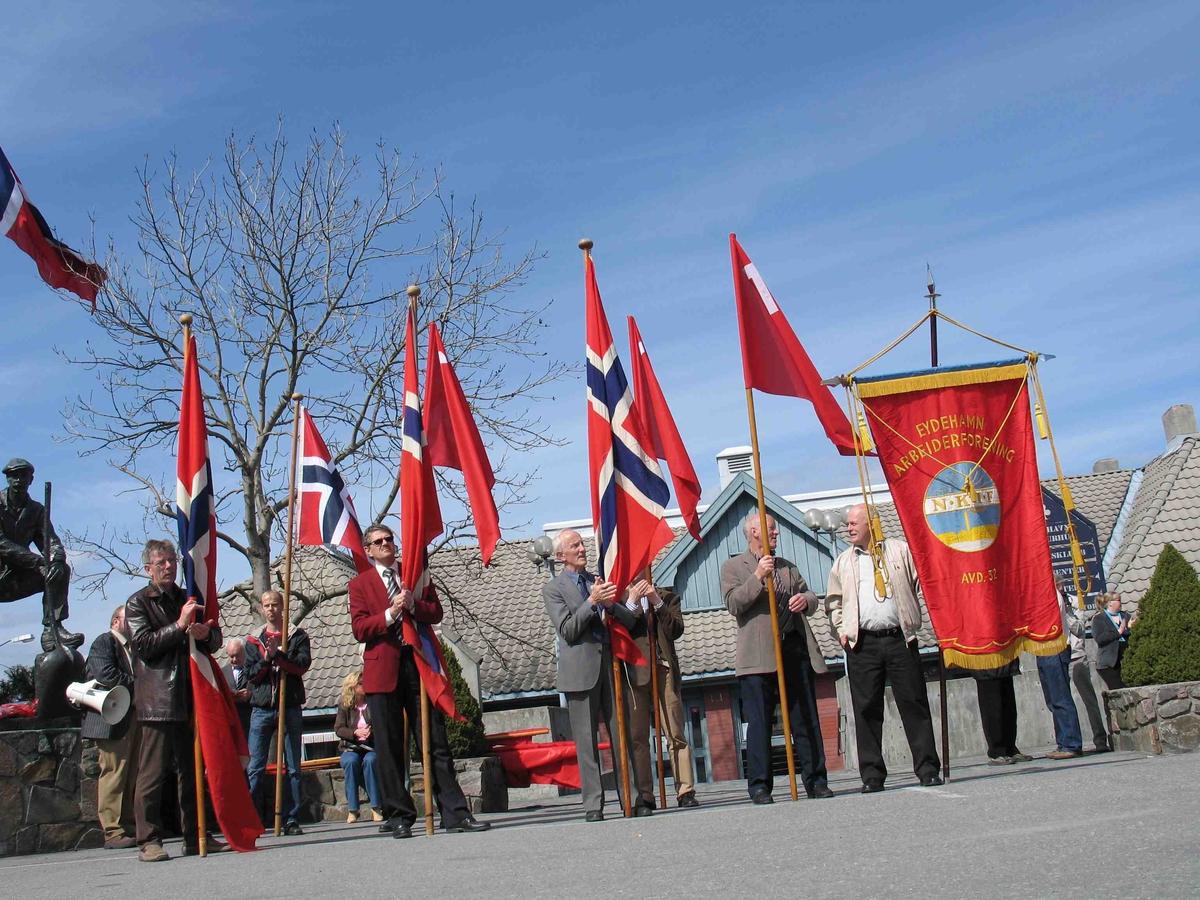 1.mai på Eydehavn. Flaggborgen og Eydehavn Arbeiderforenings fane. Litt av skulpturen Industriarbeideren t.v.
