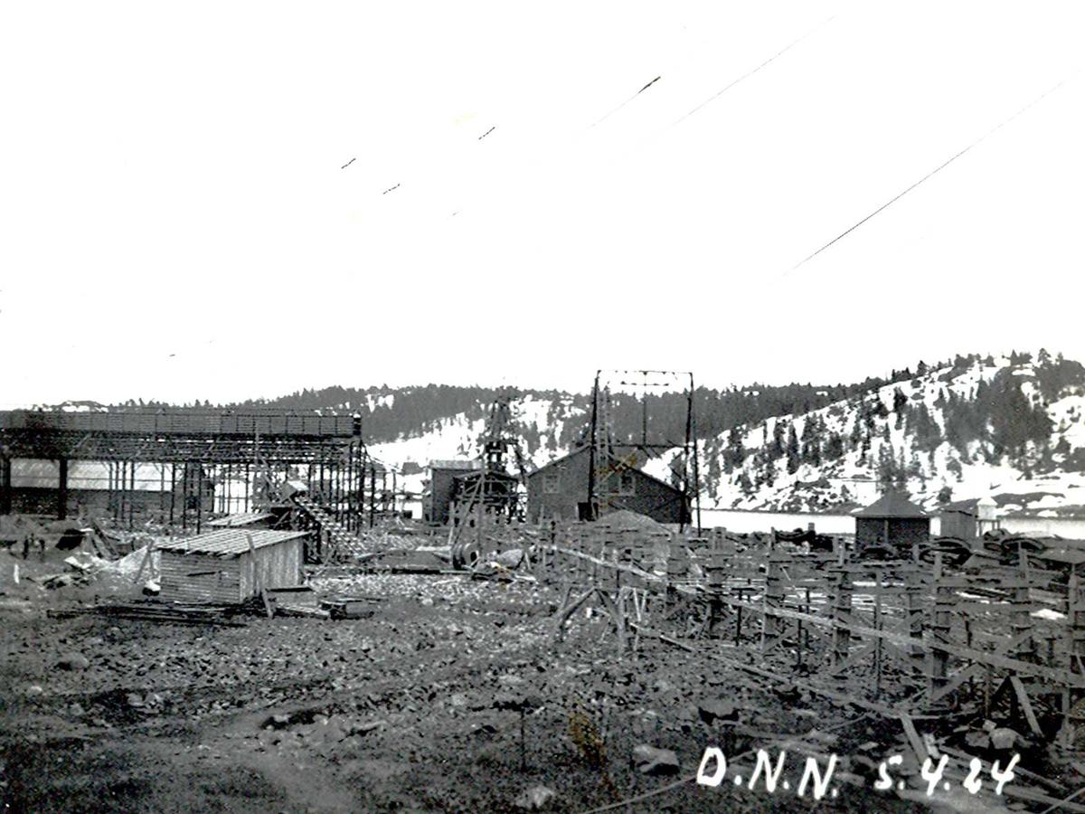 """""""05/04-1924"""" Nitriden. Stekeribygning for steking av elektrodekull under bygging. Jernkonstruksjoner. Kraner på kai i bakgrunnen. Lagerhus for bauxitt på kai. Taubanemast foran. Fyrlykt nr. 612 i Norsk fyrliste til høyre. Bygd 1894, flyttet til Friisøy i 1929. Forskalinger for bærende konstruksjoner for """"høybanen"""", skinnegang for intern transport med traller trukket av dieseldrevet lokomotiv. Tromøysund og Tromøy i bakgrunnen."""