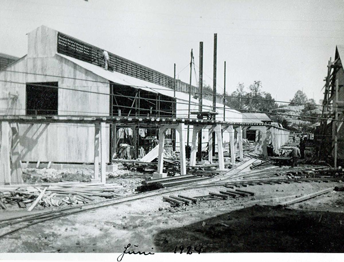 """""""xx/06-1924"""" Nitriden. Bygning for steking av elektrodekull. Bærende konstruksjoner for skinnegang, """"høybanen"""", sees foran bygningen. På bakken skinnegang. For intern transport."""