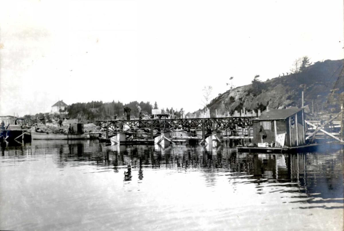 Nitriden. Bygging av kaianlegg. Smelteverkets direktør bolig på høyden til venstre. Forskalinger, jernkonstruksjoner. Dykkerlekter. Tromøysund i forgrunnen.