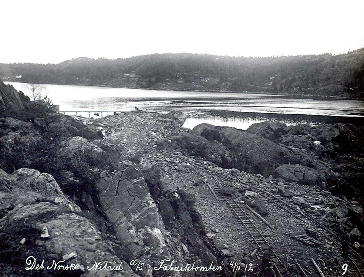 """""""04/11-1912"""" Nitriden. Planering av fabrikktomten utover mot kaifronten. Tromøysund og Tromøy i bakgrunnen. Skinneganger for bortkjøring av utsprengte steinmasser på traller."""