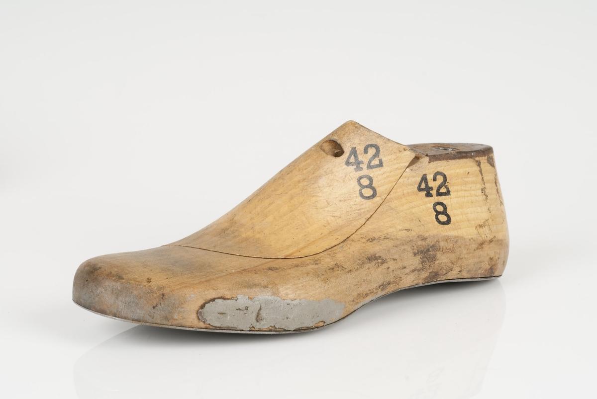 En tremodell i to deler; lest og opplest/overlest (kile). Venstrefot i skostørrelse 42, og 8 cm i vidde. Såle i metall.