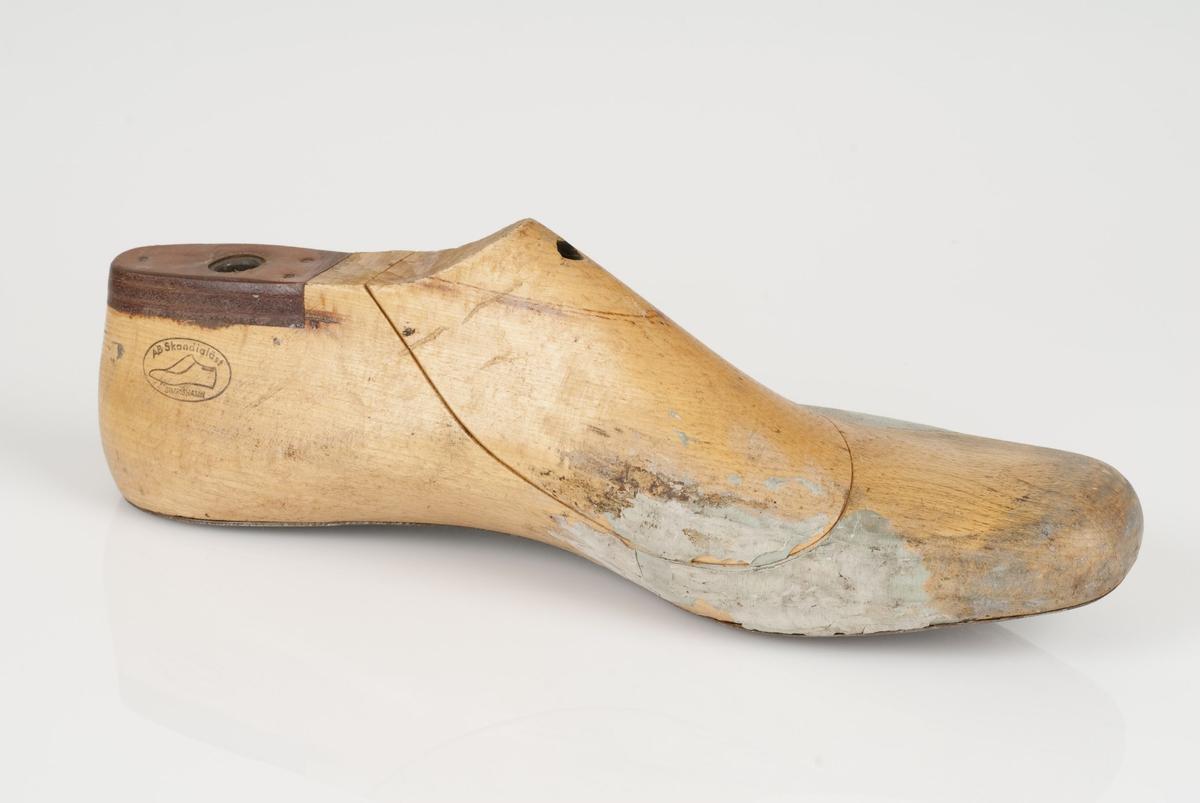 En tremodell i to deler; lest og opplest/overlest (kile). Venstrefot i skostørrelse 45, og 8 cm i vidde. Såle i metall. Lestekam i skinn.