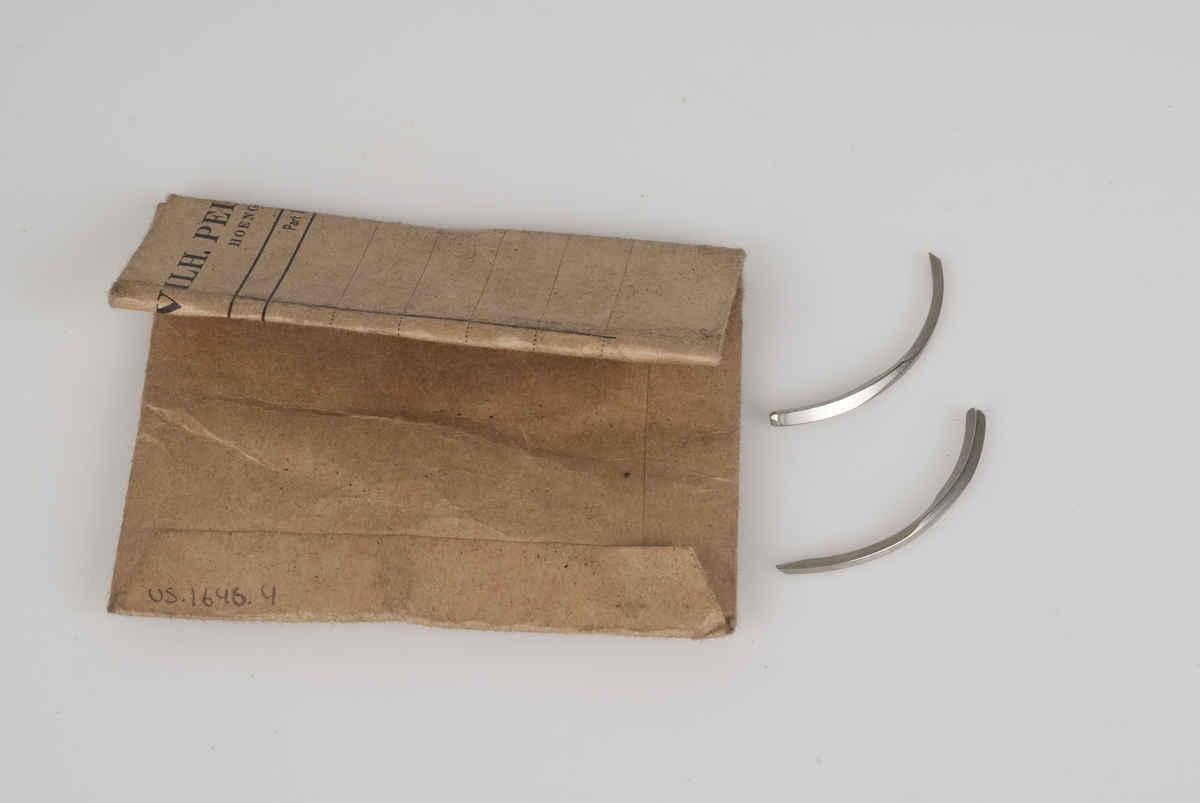 Nåler av metall i papirpose. Påført tekst på posen.