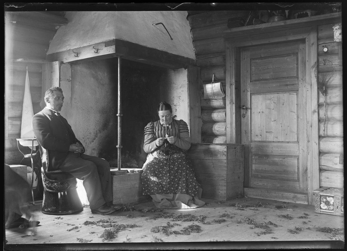 Kvinne med håndarbeide, mann sittende foran peisen.