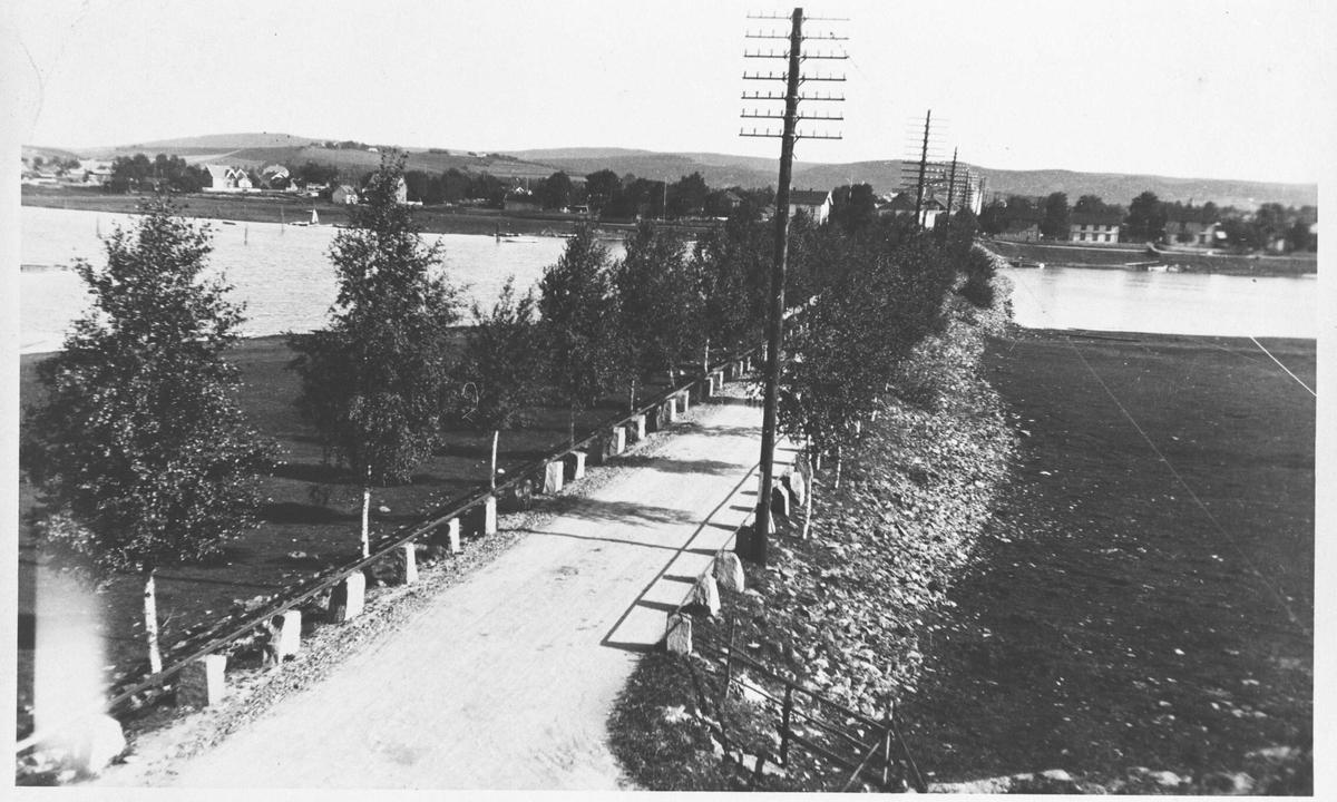 Strømsveien mot Nybrua Lillestrøm. Sett fra Sagdalsiden mot Lillestrøm. Bjerkealleen har begynt å vokse til. Stabbestein med rekkverk langs veien. Telefonstolpe.