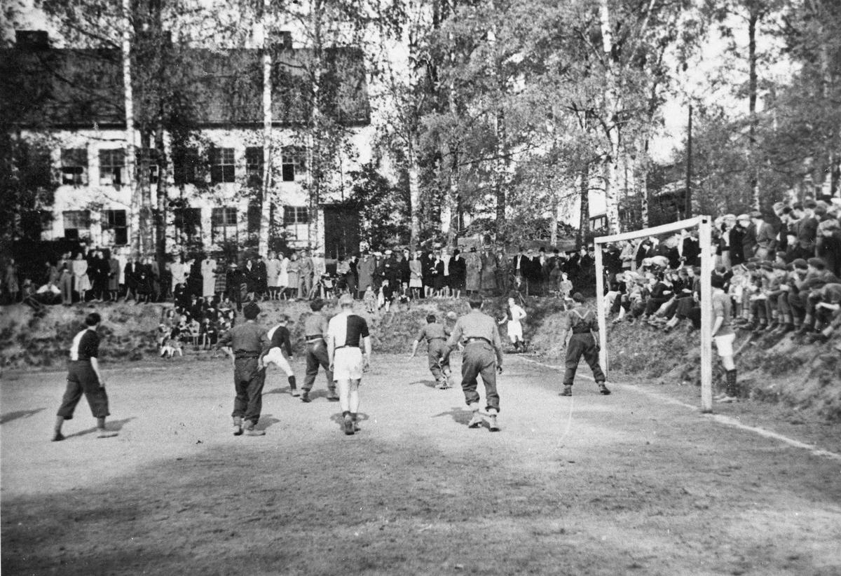 Fotballkamp mellom den norske hjemmefronten og engelske soldater. Det er bare de engelske som har uniform. Ved landsgymnaset i Eidsvoll.