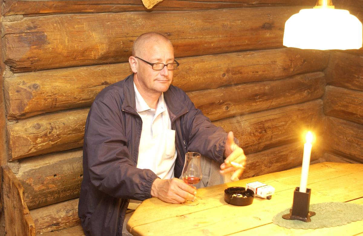 Siste 1/2 time før røykeloven trer i kraft. Mann ved bord. Med sigarett og et glass vin. Det Gamle Bageri Ost & Vinstue.