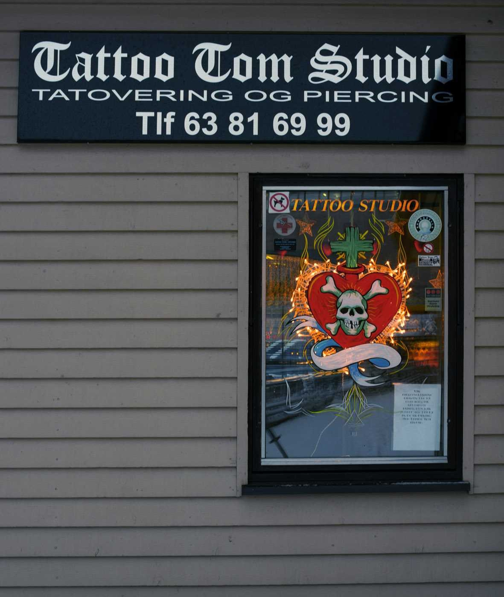 Julebelysning.  Hvite lys i krans rundt om hjerte med dødningehode og kors i vindu til Tattoo Tom Studio.