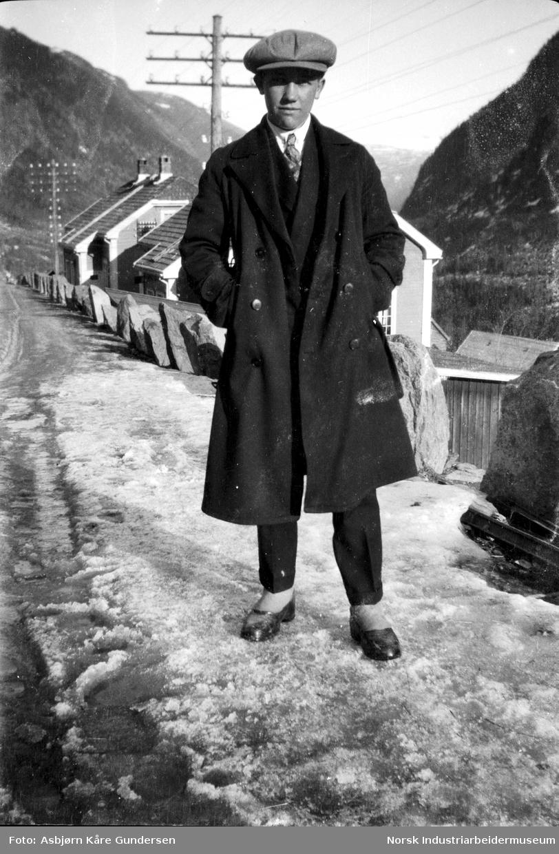 Ung mann med frakk, slips og lue i veien ved Våer. Bolighus og kraftledninger i bakgrunnen