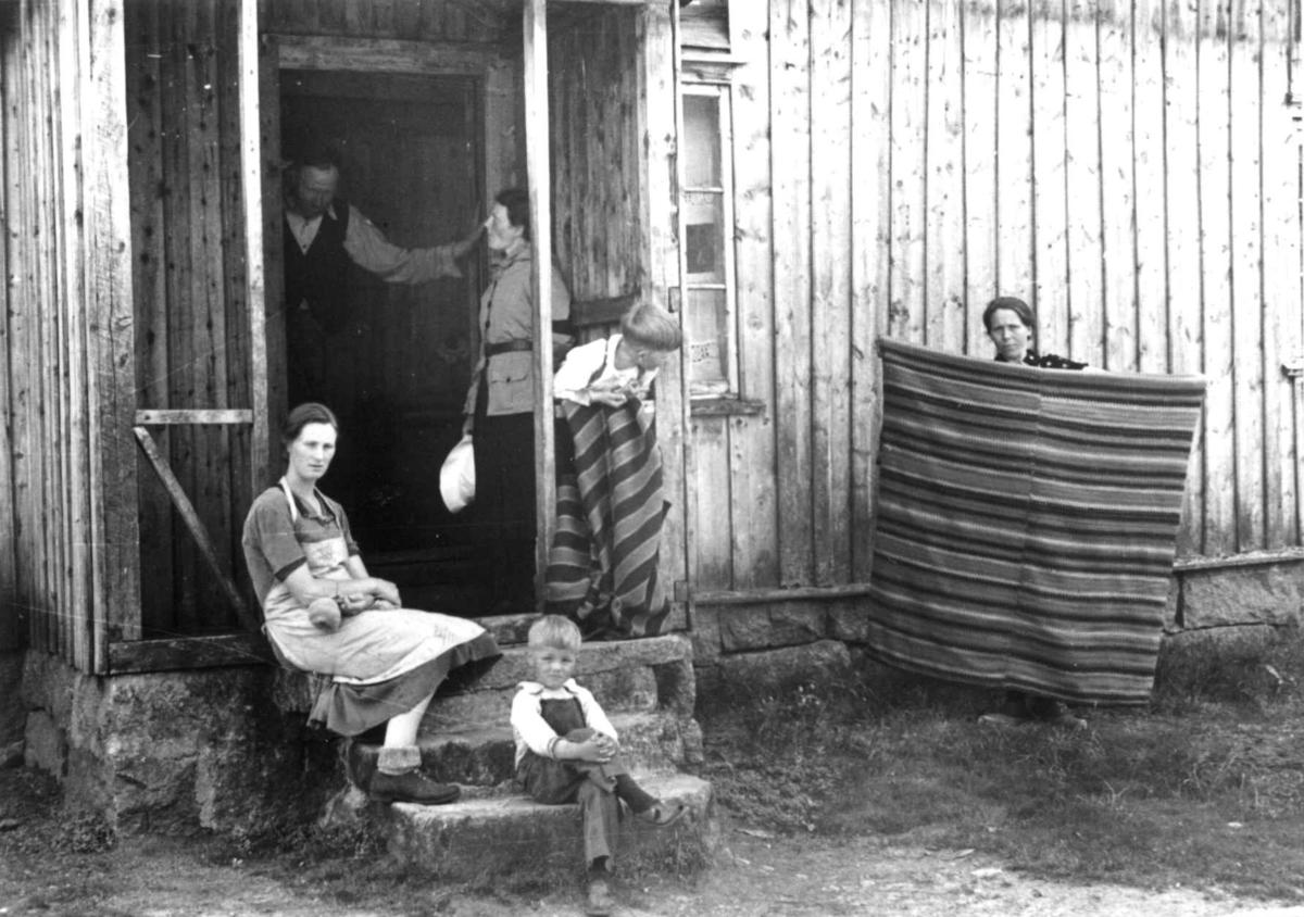 Anstein Åvitsland med flere samlet utenfor inngangspartiet til huset hans. Datteren viser frem et gammelt sengeteppe. Fjotland, Kvinesdal, 1941.